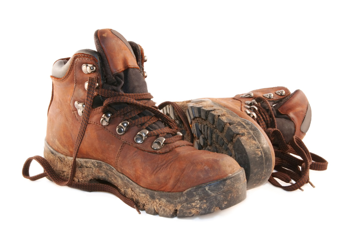 A pair of muddy brown hiking boots, isolated on white.
